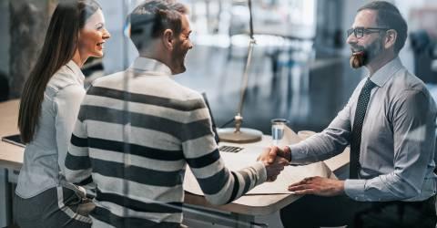 Gelukkige paar schudden handen met kredietagent in het kantoor